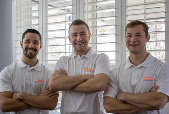 three smiling junk removal experts